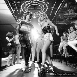 COUPLE-DISCO-DANCING-ON-ROLLER-SKATES-WEARING-TRENDY-CLOTHES-UNDER-A-MIRRORED-BALL